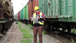 Railwayman with works documents. Railroadman in hard hat with work scheme in hands. Inspector of railway traffic on freight station makes notes. Railway employee between goods trains