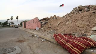 Red mattress lies on the road. Garbage lies on the street in Aqaba, Jordan. National flag of Jordan on the background