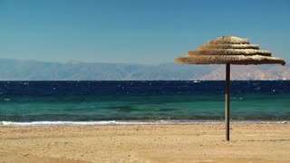 Red sea, gulf of Aqaba, umbrella on the beautiful beach. Tropical resort in Tala Bay, Hashemite Kingdom of Jordan. View on Israel and Egypt on the other coast