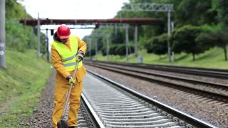 Repairman worker in yellow uniform with shovel in hands mends railway line. Railwayman in yellow uniform with shovel in hands repairs railway track. Workman with shovel on railway track