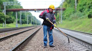 Repairman worker with shovel in hands mends railway line. Workman with shovel on railway track. Railwayman in uniform with shovel in hands repairs railway track