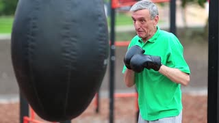 Senior man boxing with a punching bag. Active elderly boxer in boxing glove training in a boxing club. Boxer hits punching bag. Aged grey-haired man in green t-shirt training on sports ground