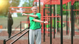 Senior man does physical exercise on sports ground. Active elderly man in green t-shirt exercising in outdoor gym. Aged grey-haired sportsman doing strenuous exercise, morning sun at background