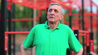 Senior man doing limbering-up on sports ground. Active elderly athlete in green t-shirt trainings in the open air gym. Aged grey-haired sportsman does strenuous exercise