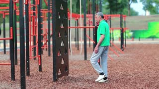 Senior man doing physical exercise on sports ground. Active elderly athlete in green t-shirt trains in outdoor gym. Aged grey-haired sportsman doing strenuous exercise