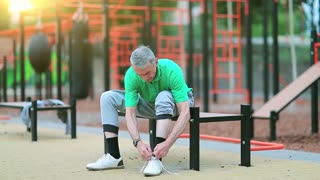 Senior man laces up his jogging shoes near sports ground. Grey-haired elderly athlete sits on the bench near outdoor gym and laces up his sneakers, beautiful morning sun with flicker at background