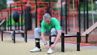 Senior man laces up his jogging shoes near sports ground. Grey-haired elderly athlete sits on the bench near outdoor gym and laces up his sneakers