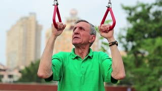 Senior man pulls up on the gymnastic rings. Sportsman doing physical exercise on sports ground. Active elderly athlete training in outdoor air gym. Aged grey-haired retiree doing strenuous exercise