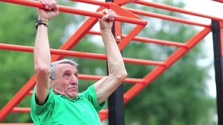 Senior man pulls up on the horizontal bar. Aged grey-haired retiree doing strenuous exercise. Sportsman doing physical exercise on sports ground. Active elderly athlete training in outdoor air gym