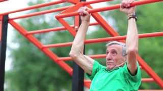 Senior man pulls up on the horizontal bar. Sportsman doing physical exercise on sports ground. Active elderly athlete training in outdoor air gym. Aged grey-haired retiree doing strenuous exercise