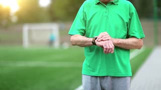 Senior man runs near football field. Active elderly man in green t-shirt runs around a football field. Man note down the time in his watch and start running.Physical activity helps to burn up calories
