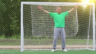 Senior man stands in football goal. Active elderly athlete in football gate. Goalkeeper in green t-shirt guards football gate on soccer field. Physical activity helps to burn up calories