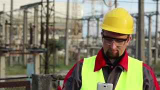 Service engineer at power plant speaks on smartphone. Worker talks on cell phone at heat electric power station near outdoor switchgear. Powerman in yellow hard hat communicates via mobile phone