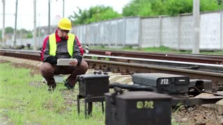 Service technician in yellow hard hat works with tablet computer. Railway worker with white tablet computer. Railway employee with tablet computer stands on railway line