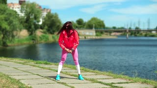 Sportswoman does physical exercise and runs on the spot. Active young woman doing exercise near lake. Girl goes in for sports, girl engaged in fitness. Physical activity helps to burn up calories