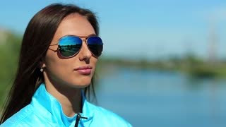 Sportswoman drinks water. Attractive girl in sunglasses drinks clean mineral water from bottle. Beautiful woman in blue sports jacket drinks water and looks around