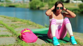 Sportswoman lies on green mat near the lake and train abdominal muscles. Girl doing physical exercises and pumps press. Woman goes in for sports, physical activity helps to burn up calories