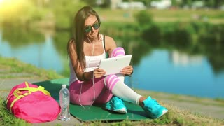 Sportswoman sits on green mat near lake and communicates via tablet computer. Beautiful girl sits near lake and talks via tablet pc. Woman in sportswear with tablet computer communicates through skype