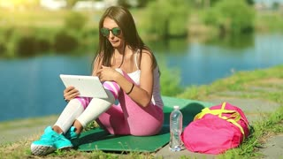 Sportswoman sits on green mat near lake and speaks via tablet computer. Girl sits near pond and talks via tablet pc. Woman in sportswear with tablet pc communicates through skype or video chat