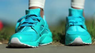 Sportswoman to laces up her jogging shoes. Runner is getting ready to runs for a long distance. Woman goes in for sports, blue sneakers close-up
