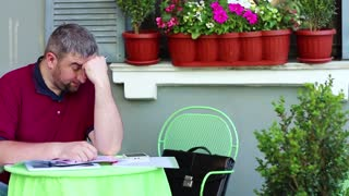 Tired and stressed businessman sits at the table in summer restaurant. Man under a stress sits in summer cafe. Smartphone, tablet pc and business papers lies on the table