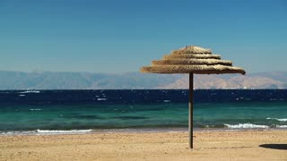 Tropical resort in Tala Bay, Hashemite Kingdom of Jordan. Red sea, gulf of Aqaba. Umbrella on the beautiful beach. View on Israel and Egypt on the other coast