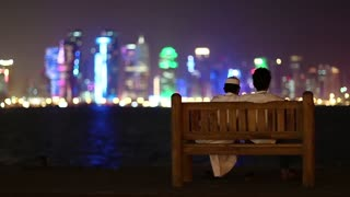 Two Muslim guys sits on bench and looks at Doha Bay, Qatar