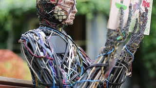 UKRAINE, KIEV, AUGUST 17, 2016: Cyborg with book in hands. Robot reads a book. Sculpture of human, made of electric wires and electronic devices