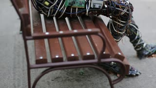 UKRAINE, KIEV, AUGUST 17, 2016: Cyborg with book in hands sits on the bench. Sculpture of human, made of electric wires and electronic devices. Robot reads a book