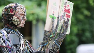 UKRAINE, KIEV, AUGUST 17, 2016: Sculpture of human, made of electric wires and electronic devices. Cyborg reads a book. Robot with book in hands