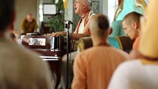 UKRAINE, KIEV, AUGUST 4, 2017: Krishna worshippers in traditional clothes in the Krishna temple, act of worship, guru plays harmonium