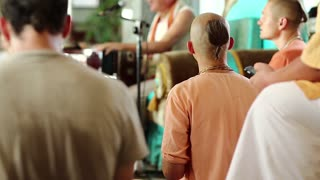 UKRAINE, KIEV, AUGUST 4, 2017: Krishna worshippers in traditional clothes sings mantras in the Krishna temple, act of worship, guru plays harmonium