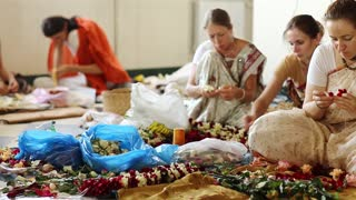 UKRAINE, KIEV, AUGUST 4, 2017: Women in Hindu traditional colorful costumes makes flower wreaths in the Krishna temple, service of the Krishna God