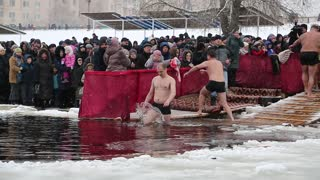 UKRAINE, KIEV, JANUARY 19, 2018: People bathes in ice-cold water of Dnieper River near Sviato-Pokrovskiy Cathedral. Traditional winter swimming in cold water at Holy Epiphany Day celebration