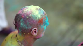 UKRAINE, KIEV, JULY 28, 2018: Head of krishnaite in many-coloured paints. People celebrate Holi - Hindu traditional festival, also known as feast of colours or festival of love