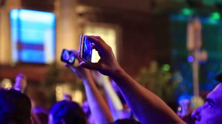 UKRAINE, KYIV, MAY 1, 2017: People makes photos and records videos with their smartphones at musical concert. People with smartphones in hands at the concert. Crowd of people dances at holiday concert