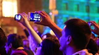 UKRAINE, KYIV, MAY 1, 2017: People with smartphones in hands at the concert. Crowd of people dances at holiday concert. People makes photos and records videos with their smartphones at musical concert