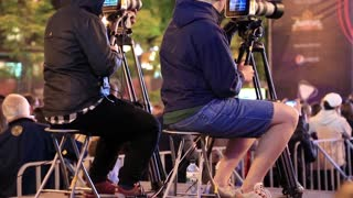 UKRAINE, KYIV, MAY 1, 2017: Video operators with camcorders on tripods records videos. Two camera operators works at musical concert