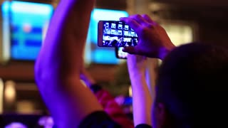 UKRAINE, KYIV, MAY 5, 2017: People with smartphones in hands at the concert. People makes photos and records videos with their smartphones at musical concert. Crowd of people dances at holiday concert