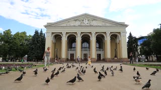 UKRAINE, POLTAVA, JUNE 19, 2017: People and pideons near Poltava academic regional Ukrainian music and drama theater named after M.V. Gogol. Poltava - city located on Vorskla River in central Ukraine