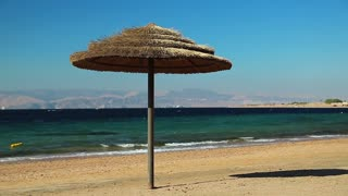 Umbrella on the beautiful beach. Tropical resort in Tala Bay, Hashemite Kingdom of Jordan. Red sea, gulf of Aqaba. View on Israel and Egypt on the other coast