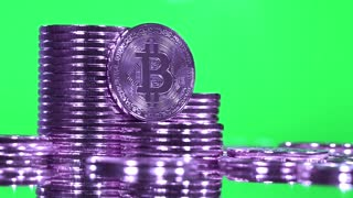 Violet Bitcoins on green background. Crypto currency Gold Bitcoin, BTC, Bit Coin, blockchain technology, bitcoin mining concept, macro shot of purple rotating bitcoins on green background