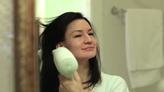 Woman dries wet hair with a hairdryer in bathroom. Attractive woman in bathroom looks into the mirror and dries hair