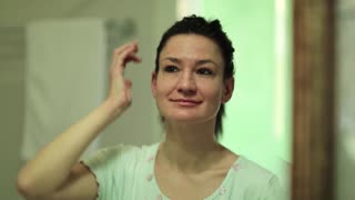 Woman looks into the mirror and applies cosmetic cream on her face. Skin care, woman puts cream on the face and looks into the mirror in the bathroom