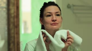 Woman looks into the mirror and wipes her face with a towel. Woman looks into the mirror in the bathroom and pretties herself