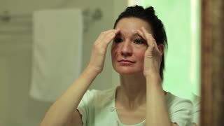 Woman looks into the mirror in the bathroom, puts cream and makes self-massage of face. Skin care, woman looks into the mirror and applies cosmetic cream on her face
