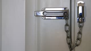 Woman moves safety chain to open the door. Woman hand and door safety chain