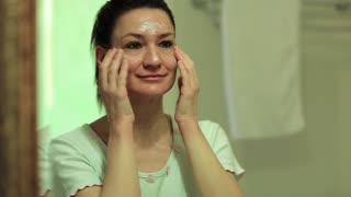 Woman puts cream on the face and looks into the mirror in bathroom. Woman looks into the mirror and applies cosmetic cream on her face. Skin care