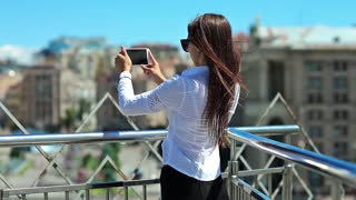 Woman records videos on smartphone. Businesswoman makes photos or records videos on his mobile phone. Beautiful girl with red cell phone