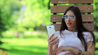 Woman sits on bench in park and uses smartphone. Businesswoman in big glasses looks at screen of his smartphone, girl with mobile phone